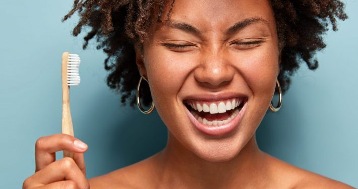 oral microbiome smiling with curly hair, laughs while has morning routines, shows bright smile, holds toothbrush, stands with bare shoulders over blue background